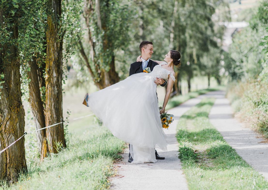 romantische hochzeitsfotografie mit brautpaar in einer sommerlichen allee