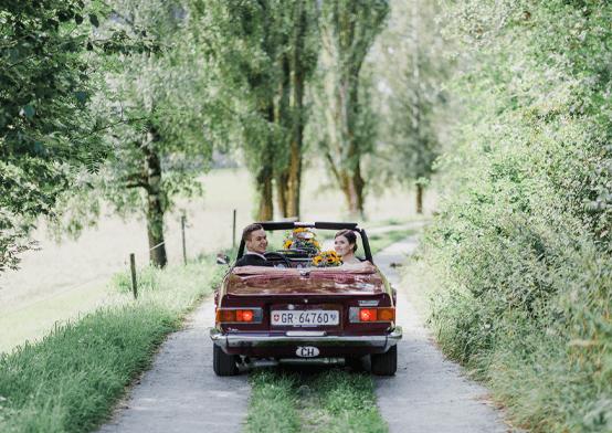 romantische hochzeitsfotografie mit brautpaar im auto in allee