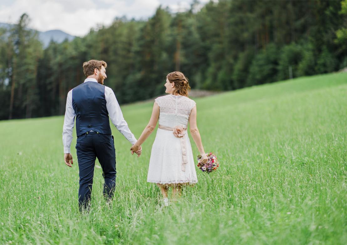 romantische hochzeitsfotografie mit brautpaar auf grüner wiese